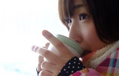 温かい飲み物をチビチビ飲む女性