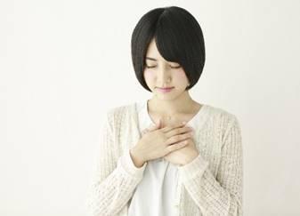 胸に手を当てて体を温める女性